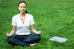 Meditating woman with laptop stock photography