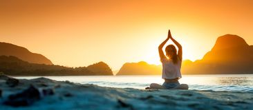 Meditating woman by the ocean with rocks royalty free stock photo