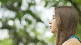 Meditating woman in park closeup, female face with closed eyes place for ad text. Stock footage stock footage