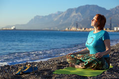 Meditating Woman on rocky Ocean Beach Mountain View on Background Royalty Free Stock Photography