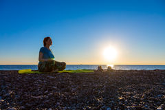 Meditating Woman on rocky Ocean Beach Sunrise background Stock Photography