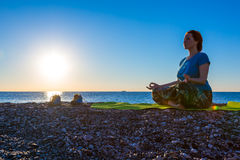 Meditating Woman on rocky Ocean Beach Sunrise background Stock Photos