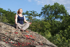 Meditating woman. Seating at the rock with rose petals royalty free stock images