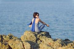 Meditating Woman in Sunglasses Stock Image