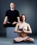 Meditating yoga trainers posing in studio Stock Photos