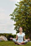 Meditating yoga woman in park on grass. Royalty Free Stock Photography