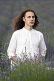 Meditating yogi. A young meditating sitting in a field of lavender Stock Image