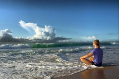 Meditating young man faces big wave Stock Photography