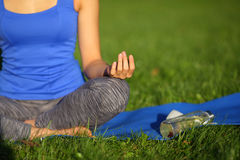 Meditating young woman in blue shirt sitting with cross-legged o. N mat Royalty Free Stock Images