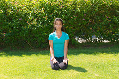Meditating young woman in lotus pose, seated on Stock Images