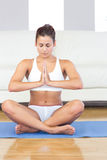 Meditating young woman sitting in lotus position on an exercise mat Royalty Free Stock Image