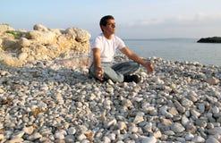 Meditation. Grown man doing yoga on the pebble beach, near the sea Stock Photo