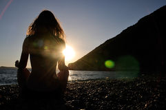 Meditation. On the beach in time of sunset with lens flare Stock Image