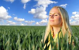 Meditation. Beautiful blond girl meditating in field Royalty Free Stock Images