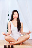 Meditation. Pretty woman in lotus pose at meditation stock image