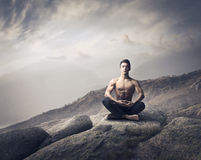 Meditation. Handsome bare-chested young man sitting on a mountain peak and meditating Stock Photo
