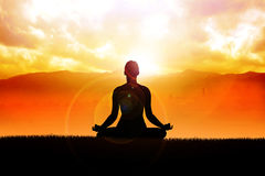 Meditation. Silhouette of a woman figure meditating in the outdoors Stock Image