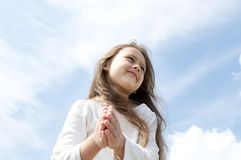 Meditation. Girl in a white jacket standing in front of chest with folded hands in the sky Royalty Free Stock Images