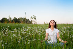 Meditation. Young woman sitting in the field of dandelions Stock Photo
