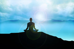 Meditation. Silhouette of a man figure meditating on the mountain Stock Photo
