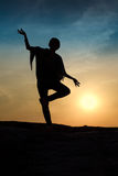Meditation. Silhouette of woman balancing on one foot and making Indian looking hand gesture. Setting sun on background Stock Photo