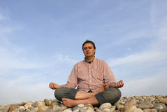 Meditation. Young man at the beach in meditation Stock Image