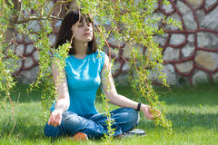 Meditation. Young girl relaxing on the green lawn Royalty Free Stock Image
