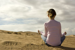 Meditation. Young woman meditating in desert sand royalty free stock photo
