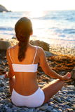 Meditation auf dem Strand am Sonnenuntergang. lizenzfreies stockbild