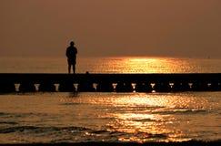 Meditation auf der Mole durch Sonnenaufgang Lizenzfreies Stockbild