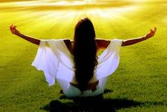 Meditation auf einem Feld in den Solarlichtstrahlen