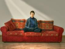 Meditation avkoppling Mogen äldre kvinna hemma på soffan, uppsättning Arkivfoto