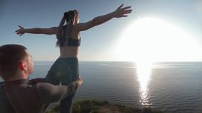 Meditation on background of sea, man and woman doing yoga exercises with beautiful pose on mountain during sunset stock video