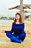 Meditation on the beach. Redheaded pretty girl meditating near the sea Royalty Free Stock Photo