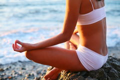 Meditation on the beach. Body of a beautiful girl in a meditation on the beach Royalty Free Stock Images