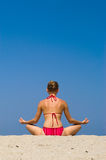 Meditation on the beach. Young blond woman in lotus position on the beach  against a blue sky - plenty of copy space Stock Photos