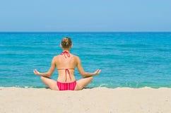 Meditation on the beach. Young woman in bikini sits in lotus position on the beach to do meditation Stock Photo