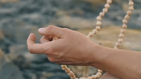 Meditation on the beads. Man meditating with beads near the sea stock video footage