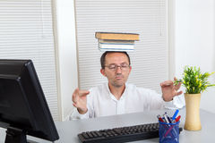 Meditation with books. Caucasian businessman in office meditate with  books Royalty Free Stock Photos