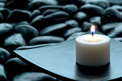Meditation Candle Burning on Plate over Stones. Meditation candle burning on an Asian inspired plate over bed of black stones in an evening religious ceremony royalty free stock image