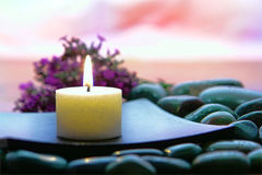 Meditation Candle Burning in Spiritual Zen Session. Meditation candle burning on a wood dish over a bed of stones with lavender flowers for a spiritual Stock Images