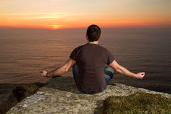 Meditation on Cliffs at sunset Stock Photos