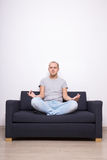 Meditation concept - tired man sitting on sofa in yoga pose Royalty Free Stock Photo