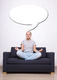 Meditation concept - tired man sitting on sofa in yoga pose and Royalty Free Stock Images