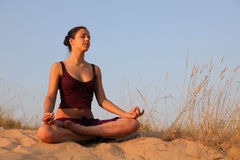 Meditation on a decline. Young woman sits in sandy dunes and meditation on a decline Royalty Free Stock Photo
