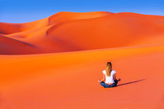 Meditation in desert. Healthy active lifestyle, young female sitting alone on hot orange sand, zen balance, beautiful nature, peace and relaxation concept stock photo