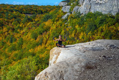 Meditation on the edge of a cliff. Girl meditates sitting on the edge of a cliff on a sunny day on a background of hills Stock Images
