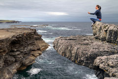 Meditation on the edge of a cliff. In Ireland Royalty Free Stock Photos