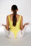 Meditation exercise. A Girl sitting on the white background royalty free stock photo