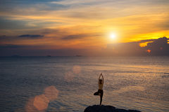 Meditation girl on the sea during sunset. Yoga silhouette. stock images